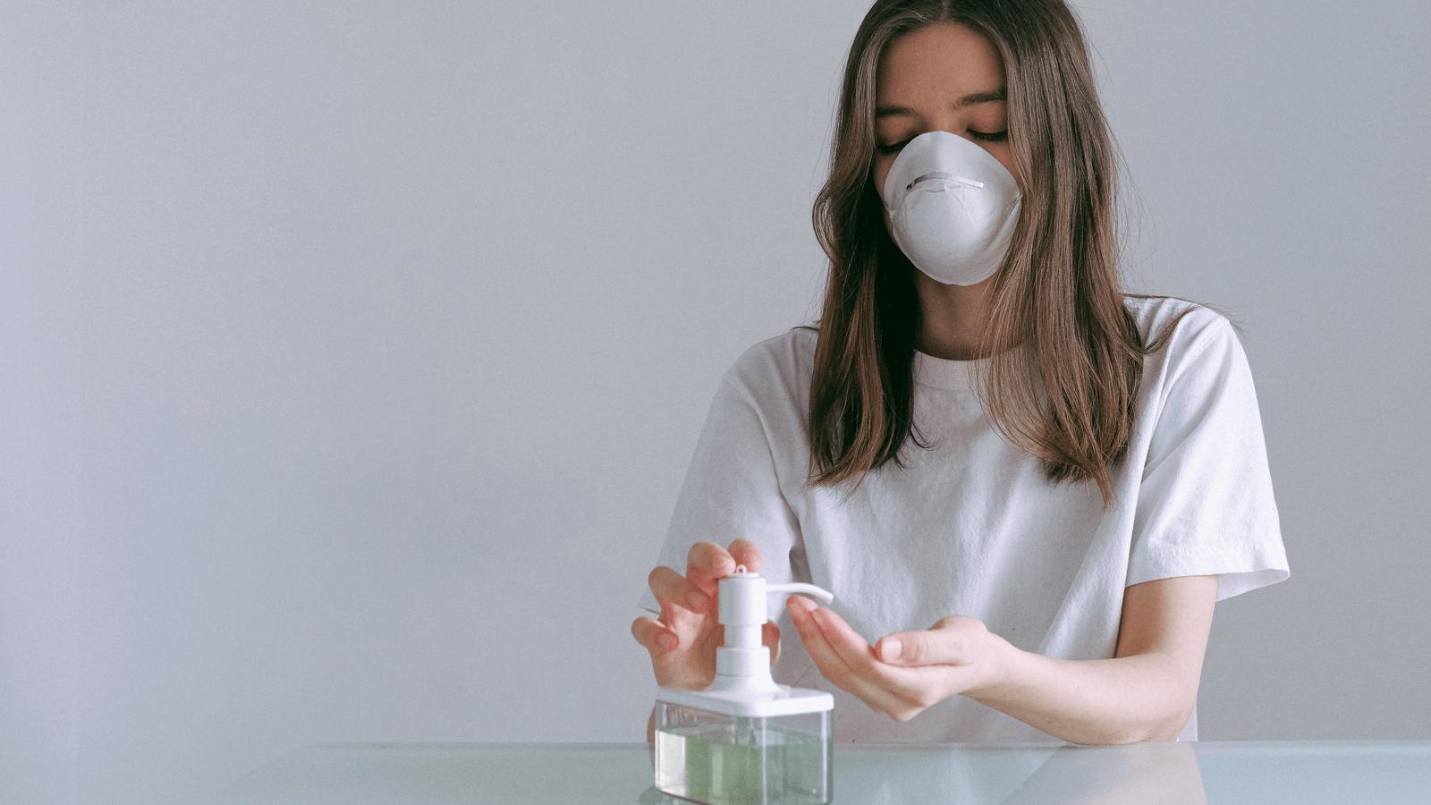Senhora com máscara a colocar álcool gel nas mãos