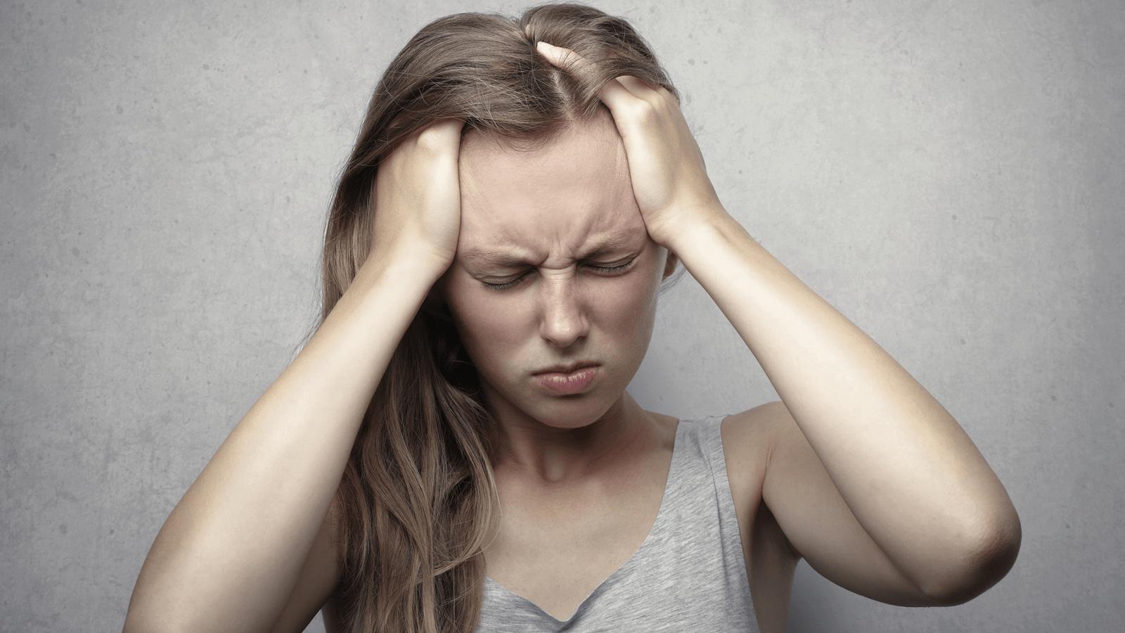 Mulher com mãos na cabeça em stresse