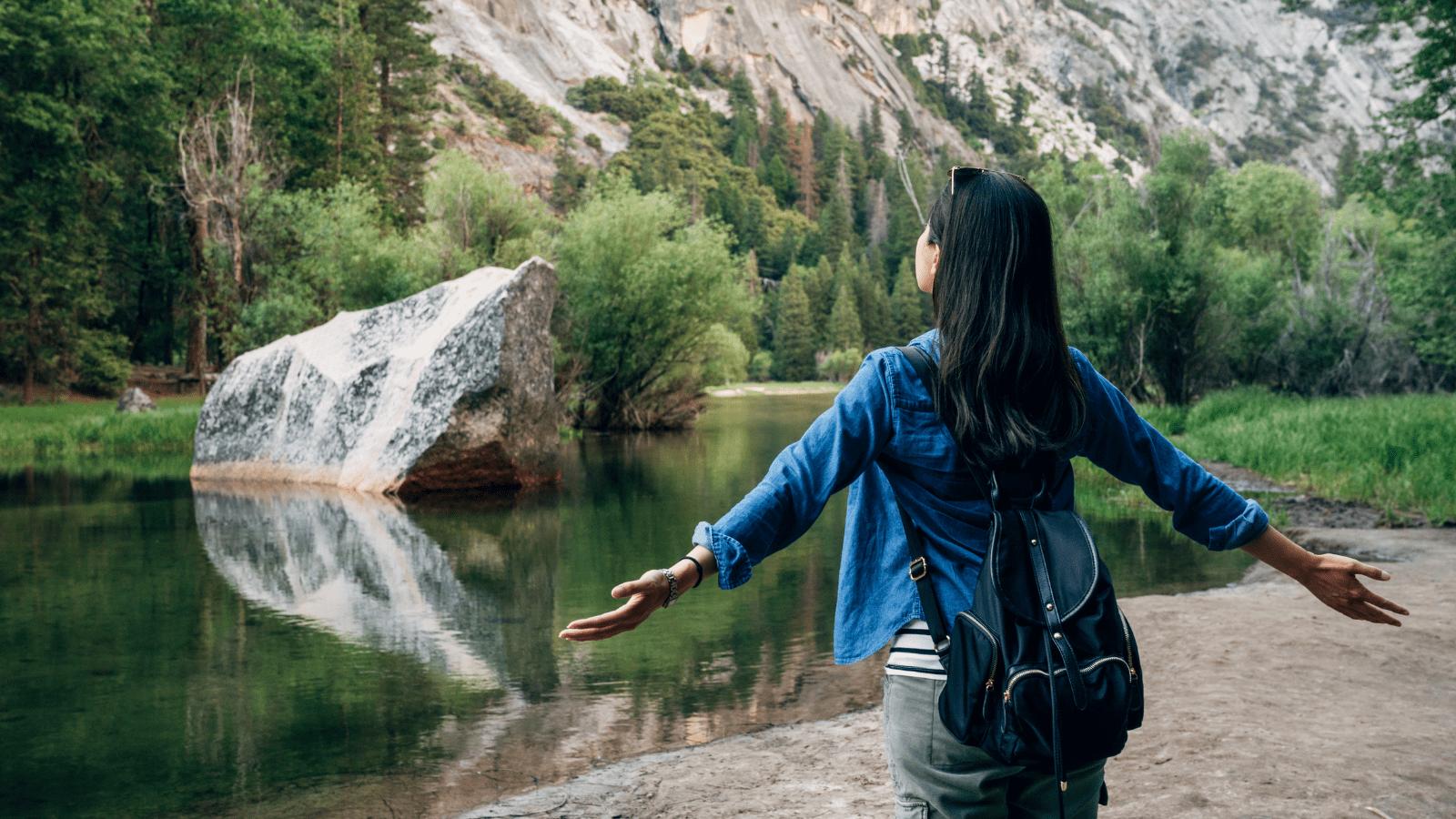 A Lei da Atração. Conquistar objetivos. Mulher de braços abertos a observar a natureza, Pensamento, Acreditar