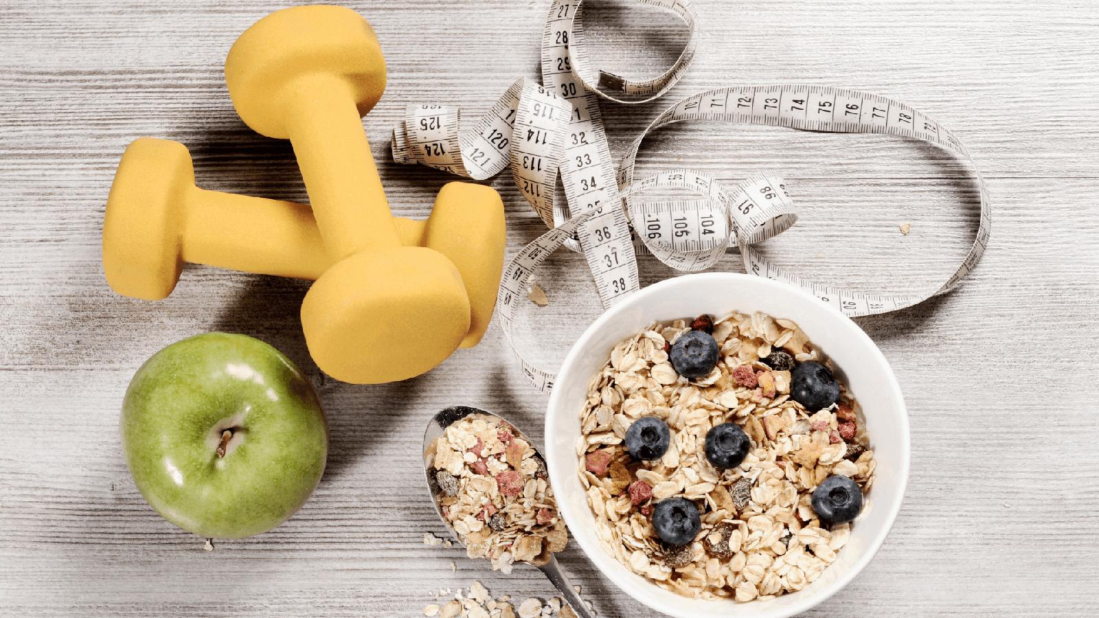 Vida Saudável com pesos, maçãs, fita métrica e prato com cereais e fruta